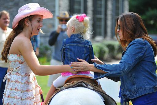 Little cowgirl riding a white pony, held by mom and staff member