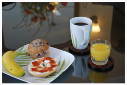 photo of a breakfast plate with bagel, banana, muffin, cup of coffee and glass of OJ