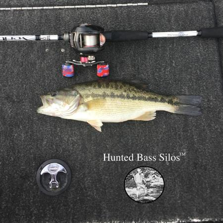 Caught bass lying in the boat next to a fishing pole