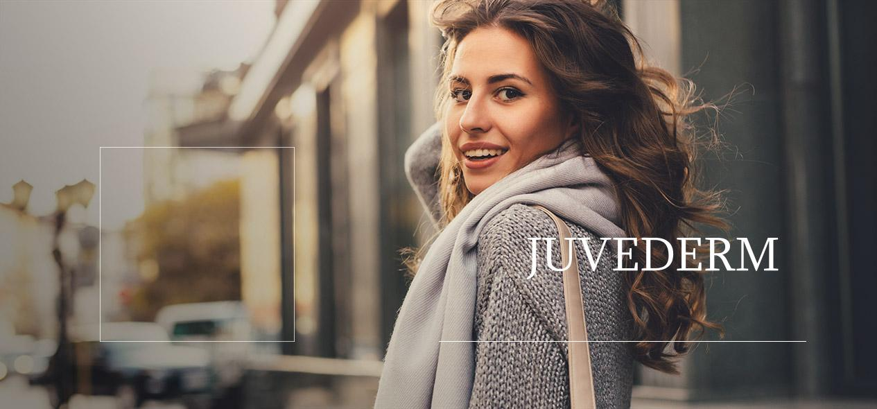 Woman walking in a city, smiling over her shoulder. Find information about the dermal filler Juvederm down below!