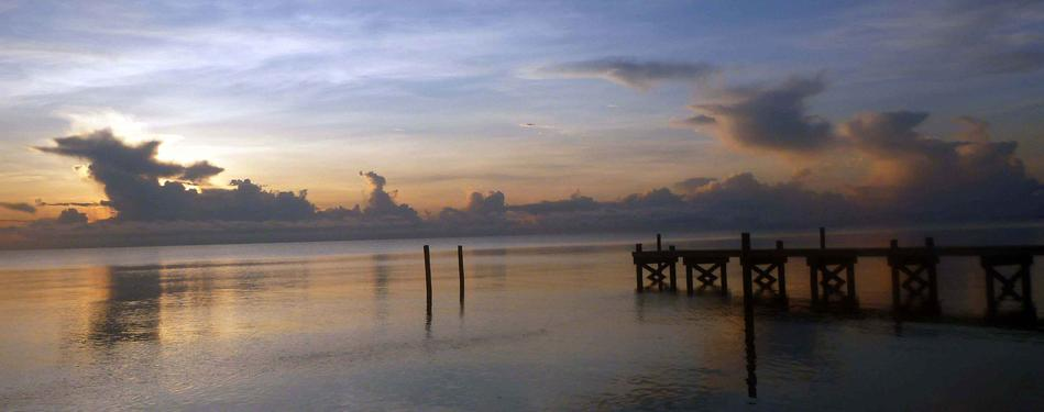 A calm and muted tone sets the scene over the Caribbean Sea at sunrise with the dock at Leaning Palm Resort. All Inclusive Vacations