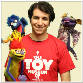 Photo of the Toy Museum's puppeteer in a red shirt with three puppets.