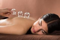 Women with brown hair laying on her left cheek as glass cups are layed on her back by hand represents cupping technique