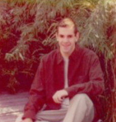Outdoor picture of David, sitting, smiling looking at camera