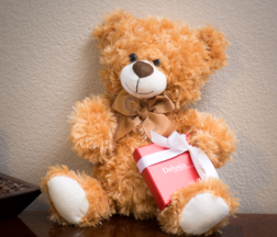 Teddy bear, bearing a gift of Delysia chocolate truffles
