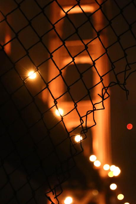 golden gate bridge through fence at night