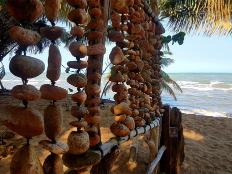 Artwork fence made from pumice stones and driftwood faces the Caribbean Sea. Private Beaches in Belize