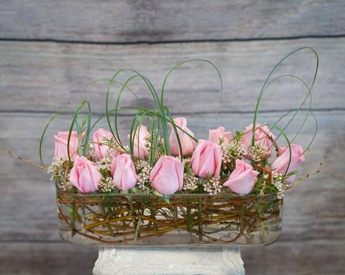 A dozen of astonishing pink roses with white wax and bear grass designed in a beautiful, long glass vase.