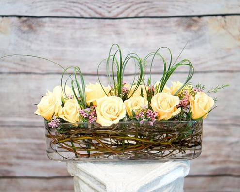 A dozen of astonishing yellow roses with pink wax and bear grass designed in a beautiful, long glass vase