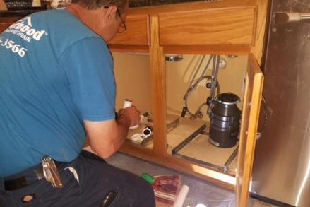 Plumber replacing garbage disposal and replacing pvc drain pipes under kitchen sink cabinet in Austin, Texas