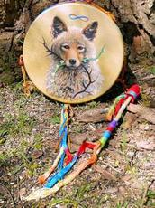 a beautiful coyote painting on a hummingbird drum