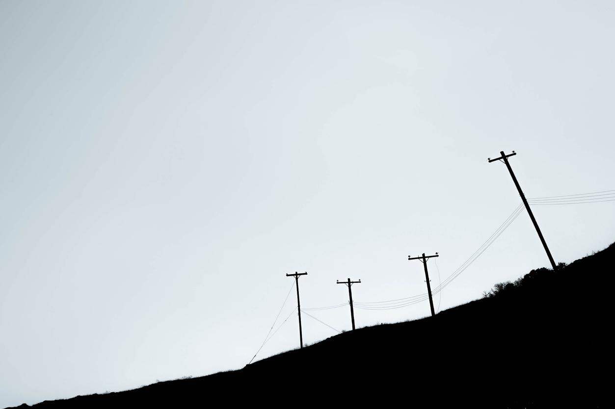 telephone poles over hill black and white
