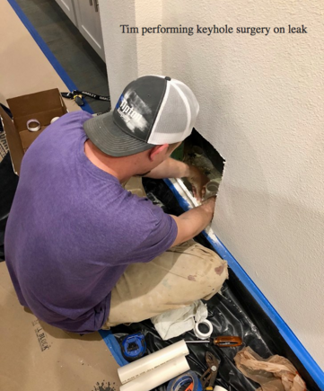 "A Plumbinator plumber sits on the floor in front of a hole in the wall just big enough for his hands plus a bit more, performing ""keyhole surgery"" on a leak"