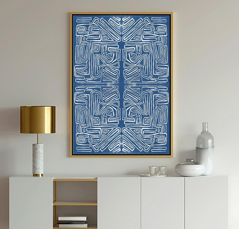 Abstract Art showing geometric shapes shades of blue and white against gray walls with a gold lamp