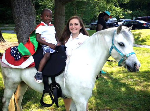 Super Hero birthday party, with small black boy riding Silver with American flag