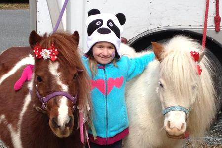 Poco and Lily, two mini horses, in winter with girl standing between them