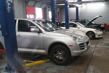 Picture of a Porsche and Mercedes benz being repaired in the shop