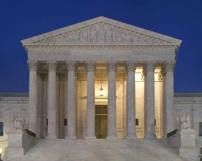portico of Supreme Court at night with a hanging light on behind pillars