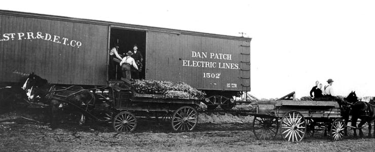 Bachman farmstead workers load produce onto a Dan Patch line boxcar for delivery to market.