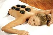 lady lying on table with towl on lower extremities with 6 hot stones on her back