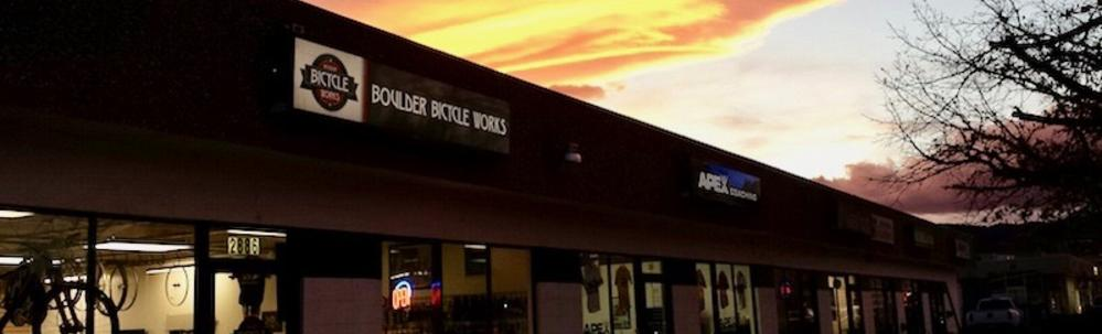 Boulder Bike Shop store front under an orange autumn sky