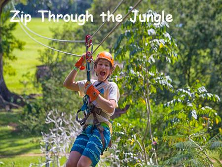 A boy on a zip line in the Belize jungle smiles for the camera. Belize Adventure Packages Available!