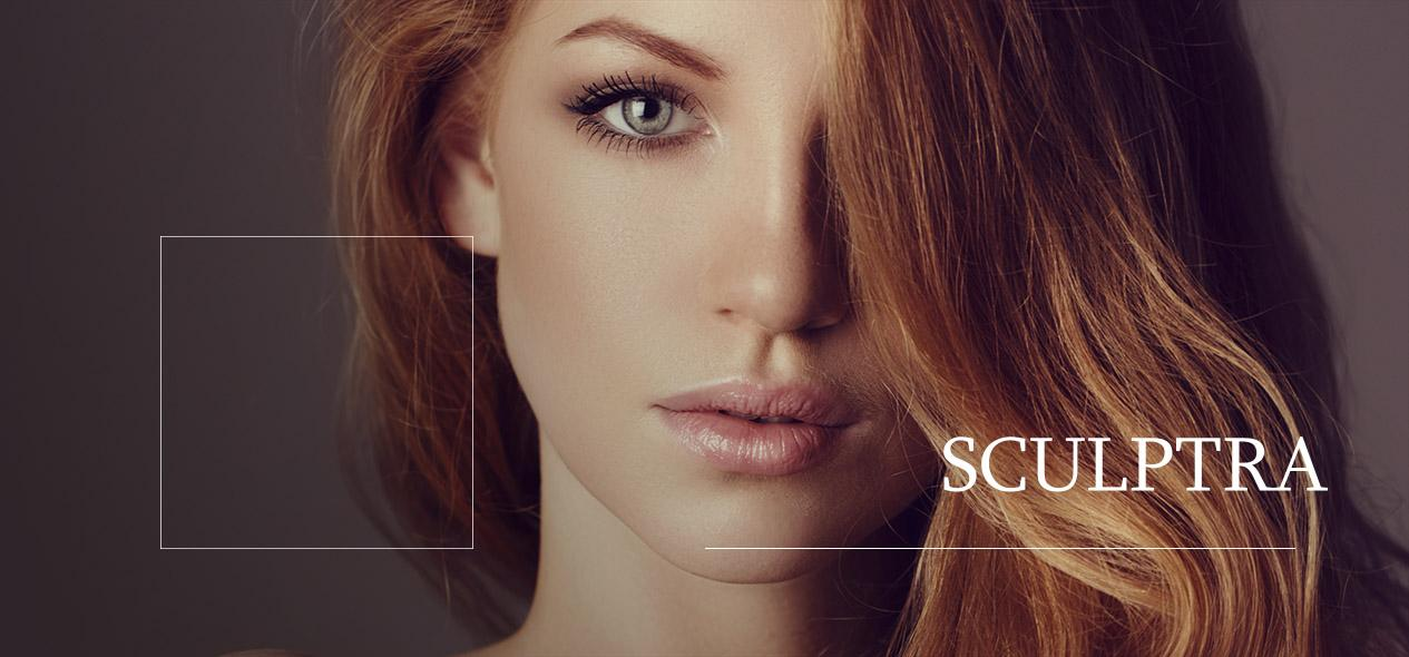 Woman with red hair looking into camera. Find information about the collagen stimulator Sculptra down below!