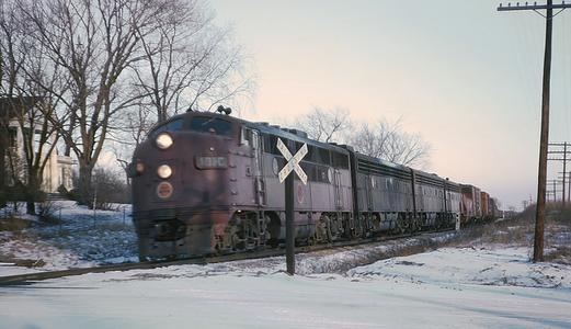 CGW 101C Westbound manifest freight No. 143 crossing Main St. and approaching the Gretns, Illinois station on December 28, 1962. Photo by Roger Puta.