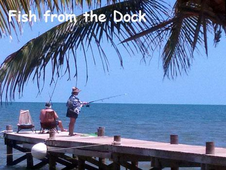 A couple enjoys some afternoon fishing from the dock in front of Leaning Palm Resort in Belize. All Inclusive Vacation Packages