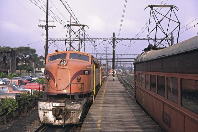 "South Shore ""800"" No. 802 is pulling thru the Gary, Indiana depot in August of 1980. On the South Shore, the big locomotives were known as the ""800's"", not Little Joes as they were known on the Milwaukee Road. Photo by Drew Jacksich."