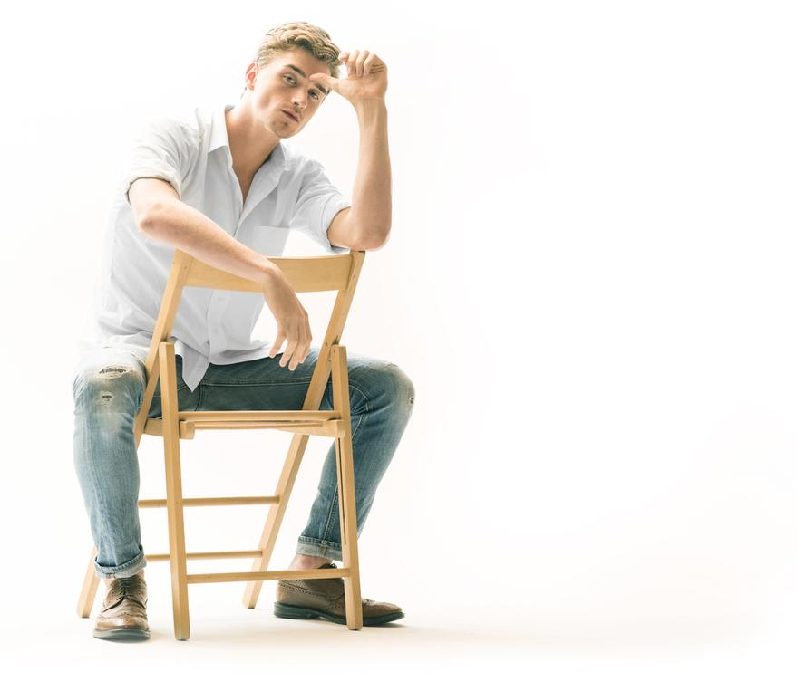 A picture of the Conner sitting backwards in a chair.