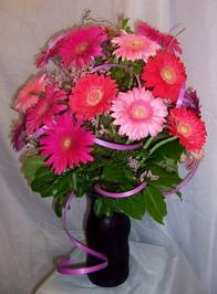 Vase arrangement designed in a color glass vase with two dozen gerbera daisies, curly willow, wax flower, and a variety of foliage.