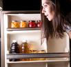 "alt=""woman looking inside her refrigerator"""