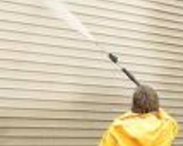 technician pressure washing vinyl siding