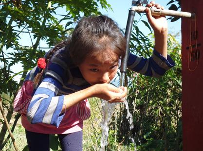 Young Gurkha child drinking from a GWT water tap in Nepal