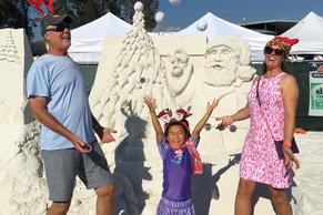 Rich, Ali, and Chloe jumpingin front of a sand sculpture on Siesta Key Beach.