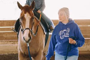 A volunteer leading a horse
