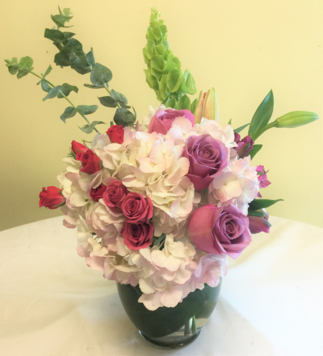 Vase arrangement designed with hydrangea, bells of Ireland, spray roses, lilies, roses, and a variety of foliage