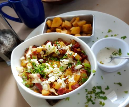 Wild Canes breakfast hash surrounds a poached egg topped with feta and fresh cilantro.