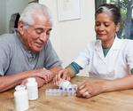 Image of female medical healthcare provider assisting older male adult with filling weekly medication box.