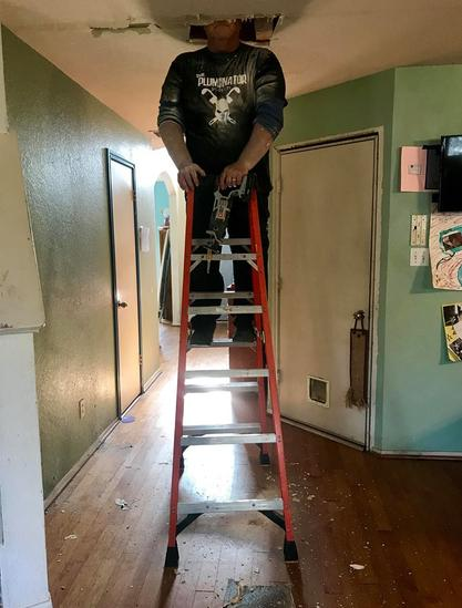A plumber stands on a ladder inside a home's hallway. His head is not visible because it is in a hole in the ceiling as he looks for water leaks.