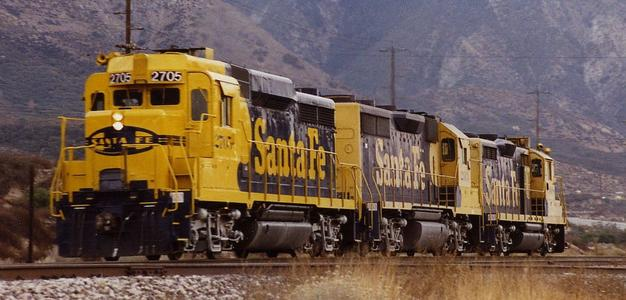 A trio of Santa Fe Railroad EMD GP units — a GP30 (in the lead), a GP35 and a GP20 — run light up Cajon Pass in California in the late 1980s.