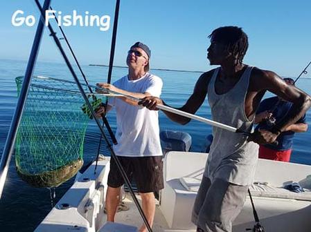 A tourist catches a big fish with the help of a Belize local guide. Fishing can be added to your Belize beach vacation.