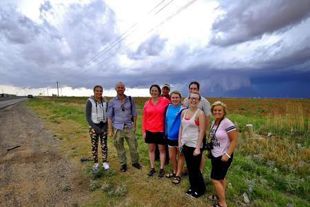 Storm Chasing Tour Happy Guests with wall cloud behind them