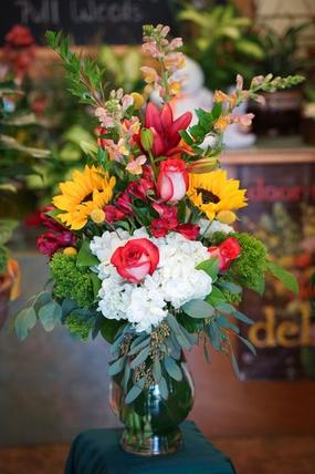 White hydrangea, vibrant sunflowers and snapdragon are designed in this traditional style vase arrangement. Orange toned roses and seeded eucalyptus are added as finishing touches.