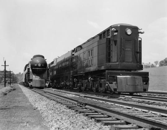 Norfolk and Western Railway's the Powhatan Arrow headed by streamlined engine No. 605, a Class J Northern type 4-8-4 locomotive, passing engine No. 2300, the Jawn Henry.