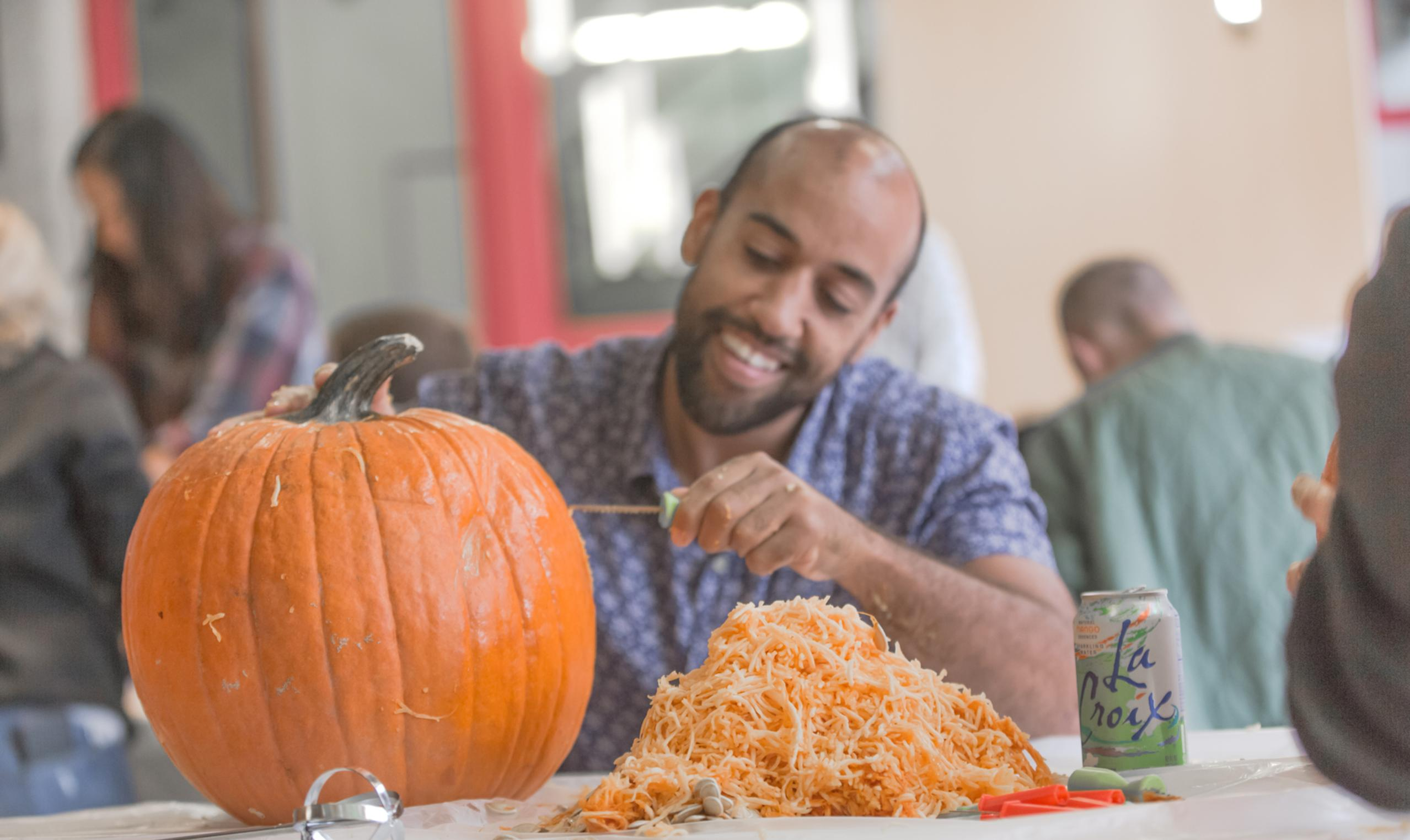 young ethnic male carving pumpkin office scenario