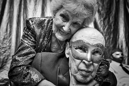 A picture of a senior couple wearing mardi gras masks.