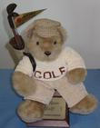 Picture of Optic Bear Trophy - stuffed teddy bear with cap, golf bag with two clubs on shoulder sitting on top of wooden base displaying engraved names of past winners