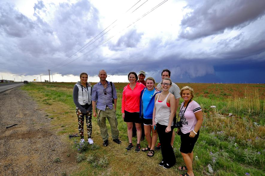 Happy storm chasing tour guests with wall cloud behind them